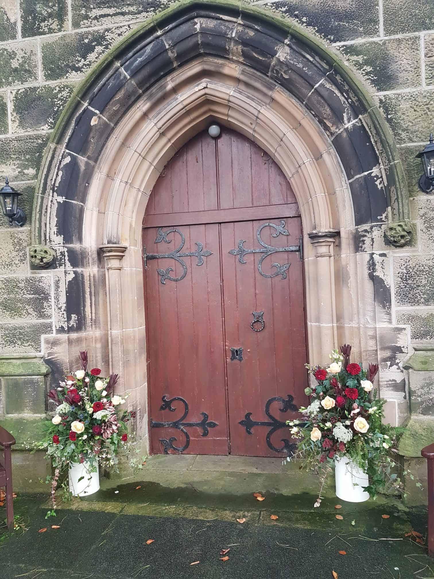 Flowers beside the church entrance - milk churns