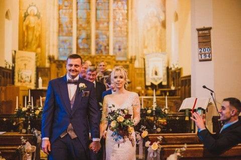 Married - walking down the aisle - flowers in shot