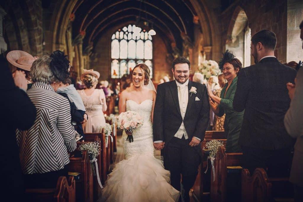 Walking down the aisle, bride bouquet in shot