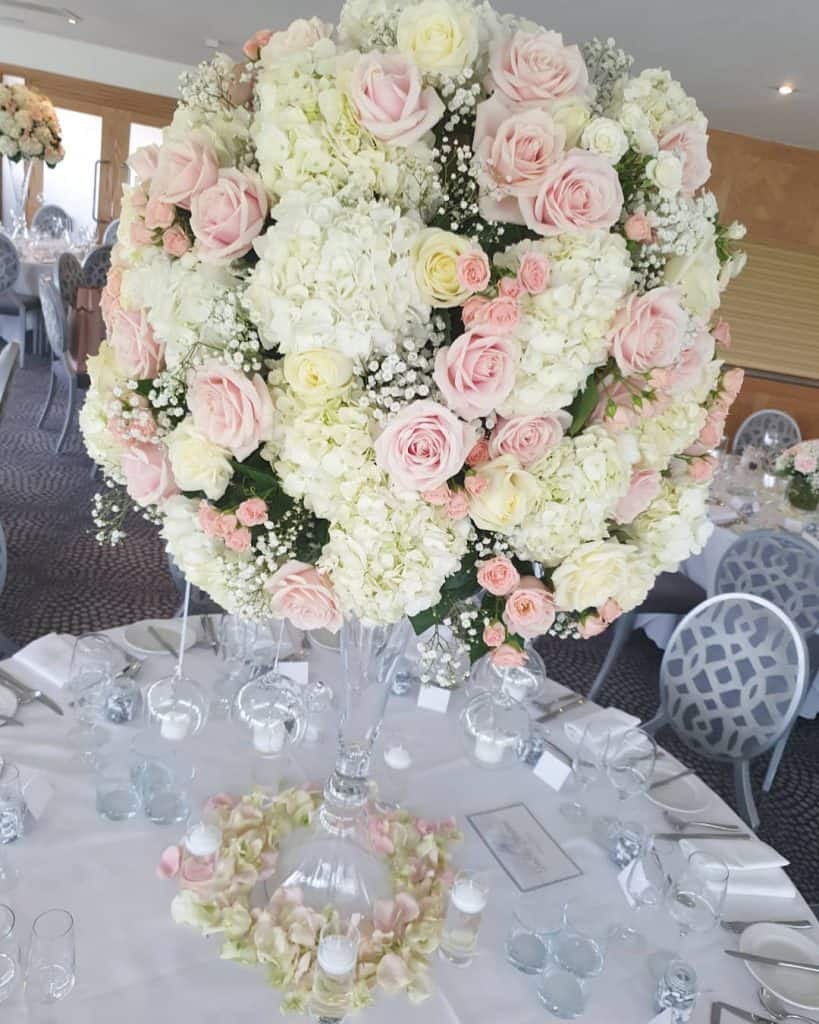 Table Centrepieces - huge ball of flowers standing on a tall glass vase