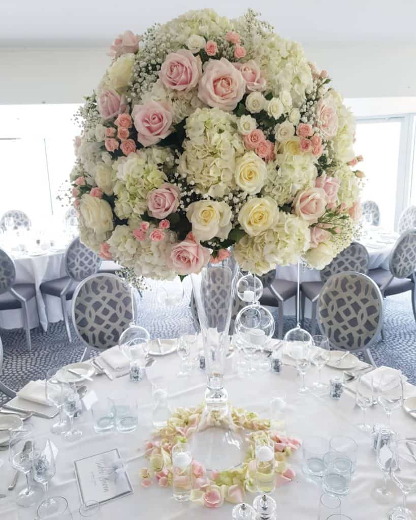 Table Centrepieces - huge ball of flowers standing on a tall glass vase, with hanging glass baubles