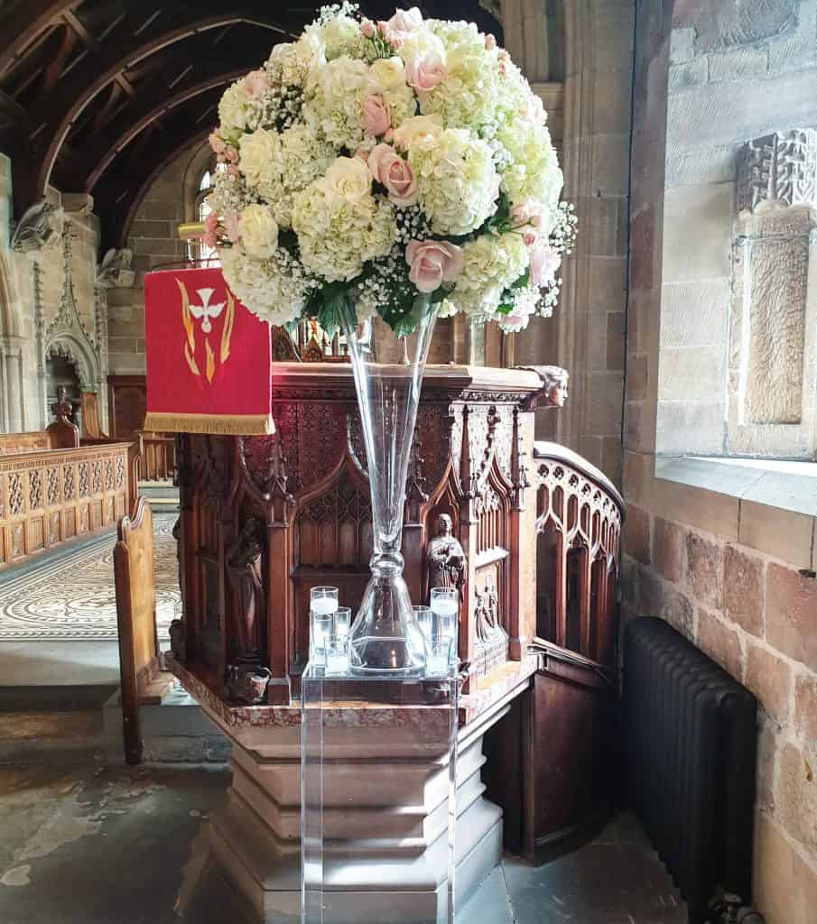 Large centrepiece arrangements on clear stands with huge glass vases